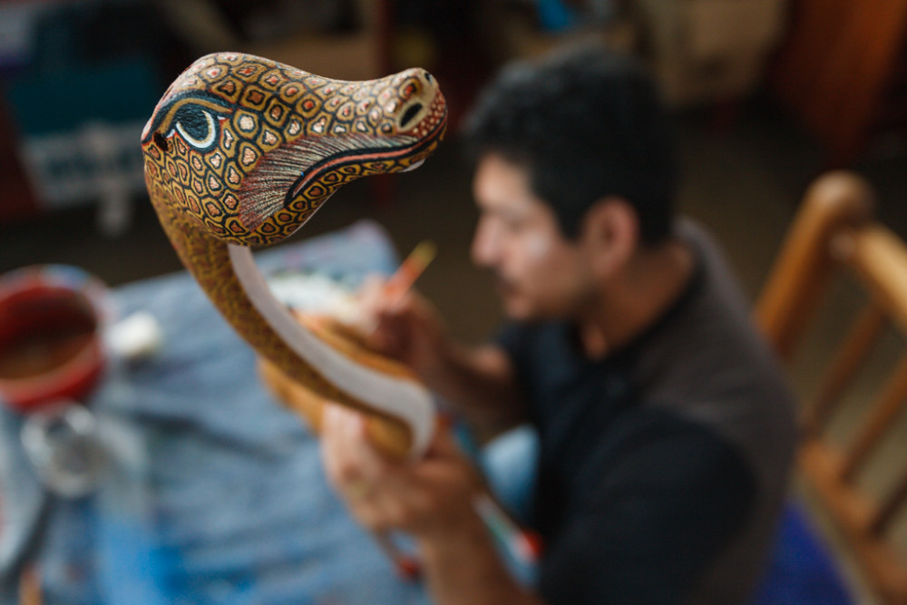 "Artisan crafting wooden figures called "" alebriijes, ""San Antonio Arrazola, Oaxaca, Mexico"