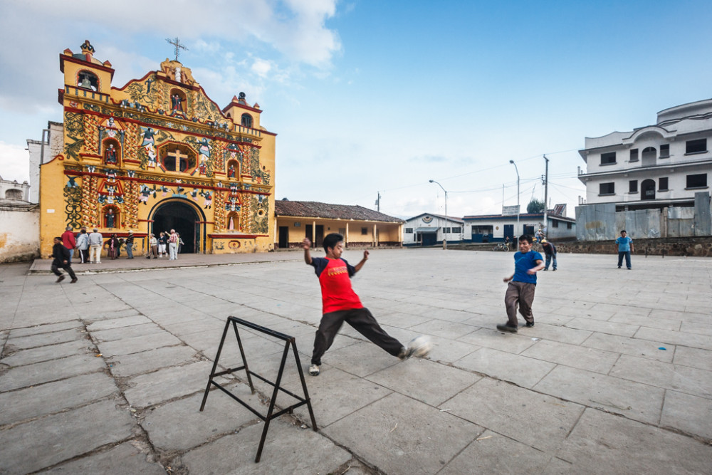 Men playing soccer in front of the colorful yellow folk art church, San Andrés Xecul, Guatemala