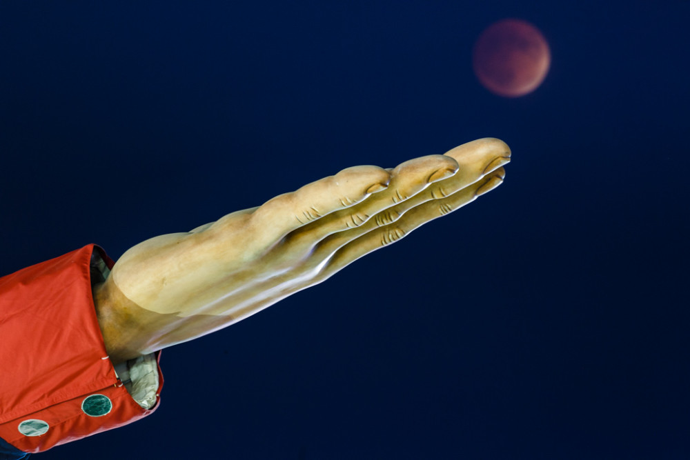 Superman lunar eclipse that was also a blood moon and a harvest moon near hand of Big Tex, State Fair of Texas, Fair Park, Dallas, Texas, USA