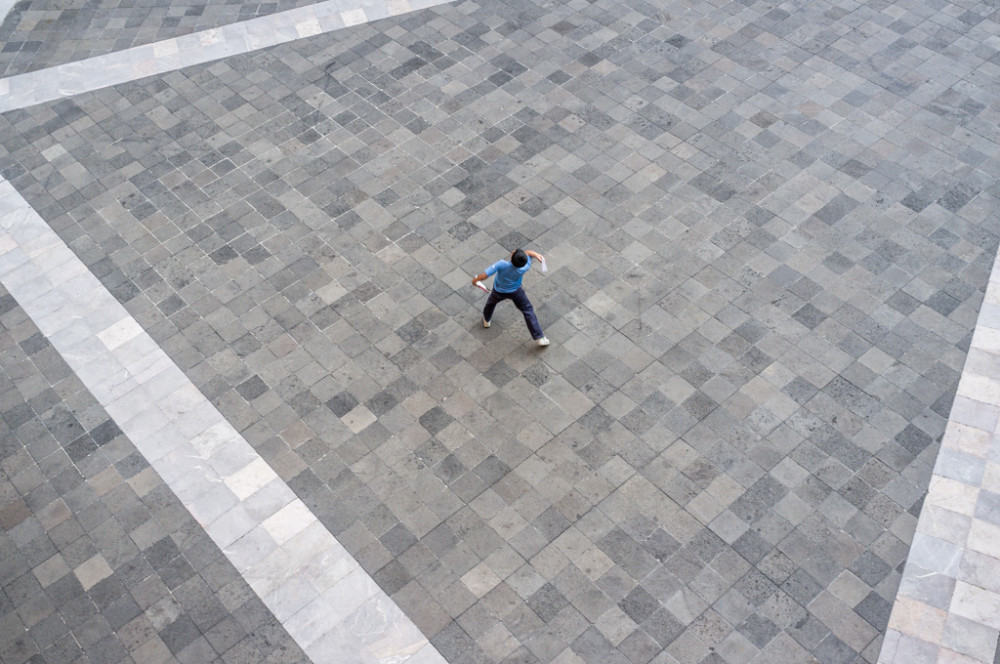 Boy throwing paper airplanes in courtyard, National Palace, Mexico City, Federal District, Mexico.