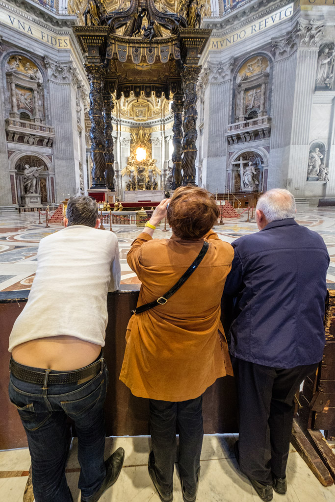 Tourist showing butt crack while viewing altar at St. Peter's Basilica, Rome, Lazio, Italy