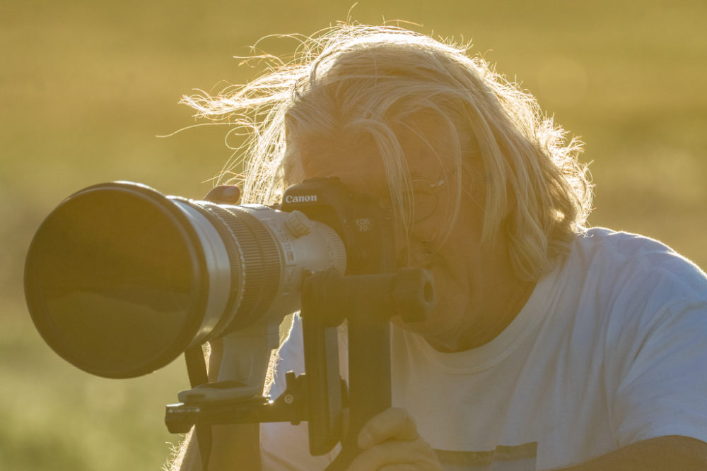 Photographer backlit by setting sun, Vermejo Park Ranch, New Mexico, USA.