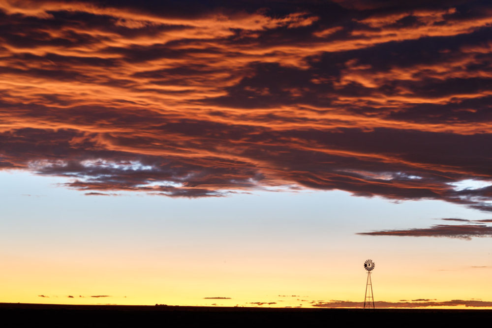 Silhouette of windmill on prairie at sunset, Rita Blanca National Grasslands in Texas Panhandle, Texas, USA.