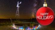 Windmill with holiday lights on stock tank beneath night stars and Milky Way, Rita Blanca National Grasslands, Texas, USA.