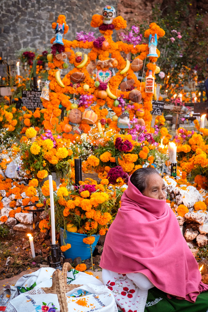 Woman in shawl amidst marigolds and small altar at cemetery during Day of the Dead on Isla de Janitzio, Lake Pátzcuaro, Pátzcuaro, Michoacán de Ocampo, Mexico.