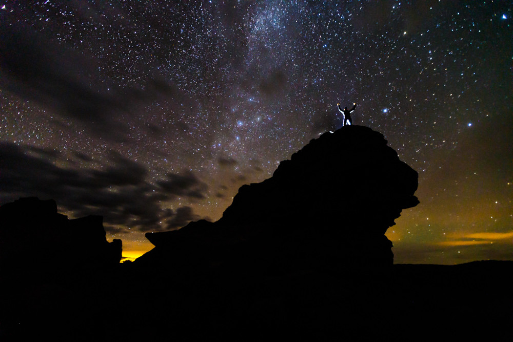 Backlit man on Castle Rock with night sky and stars, Vermejo Park Ranch, New Mexico, USA.