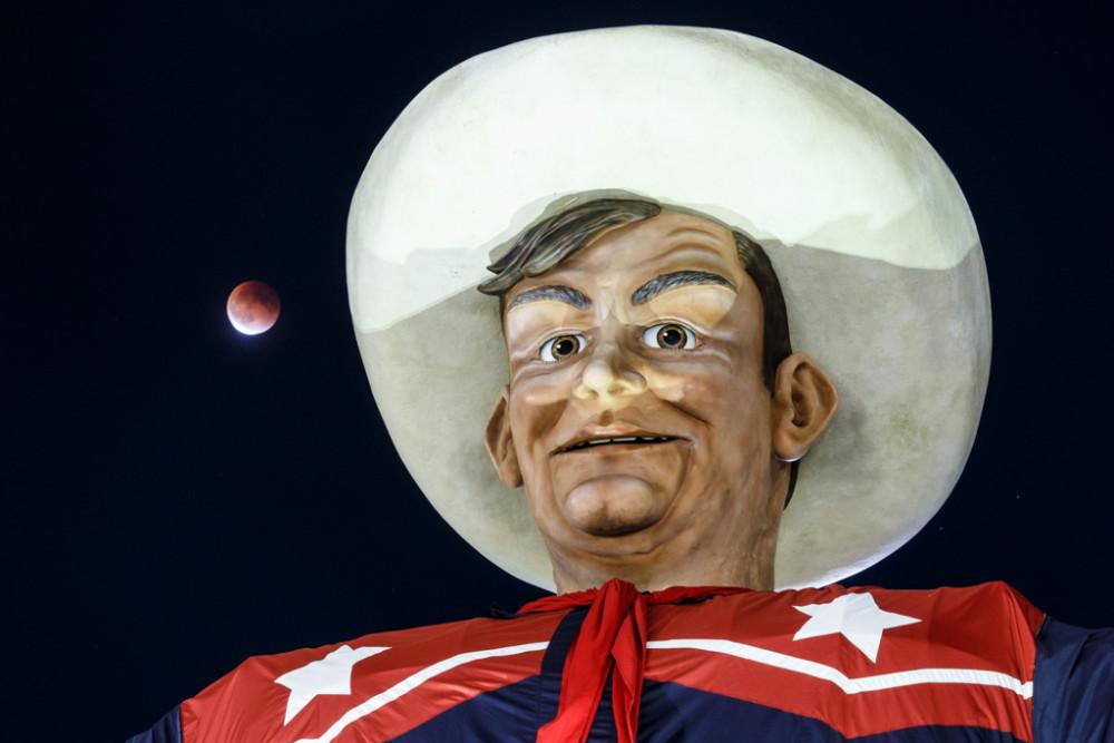 Superman lunar eclipse that was also a blood moon and a harvest moon near hand of Big Tex, State Fair of Texas, Fair Park, Dallas, Texas, USA